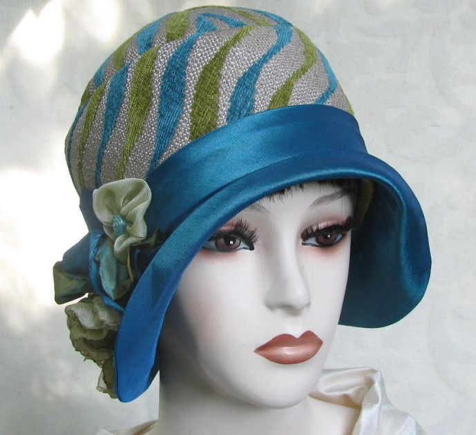96c3607c69f 1920s style cloche hat in a art deco swirling pattern design in avocado and  turquoise. The hat is detailed in a shimmering pleated taffeta band and  turned ...